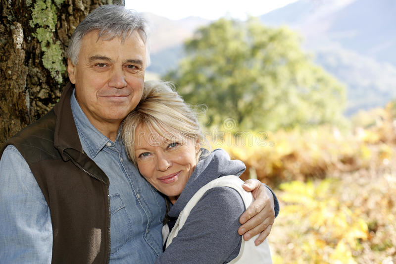 Glimlachend hoger paar die in bos omhelzen royalty-vrije stock fotografie