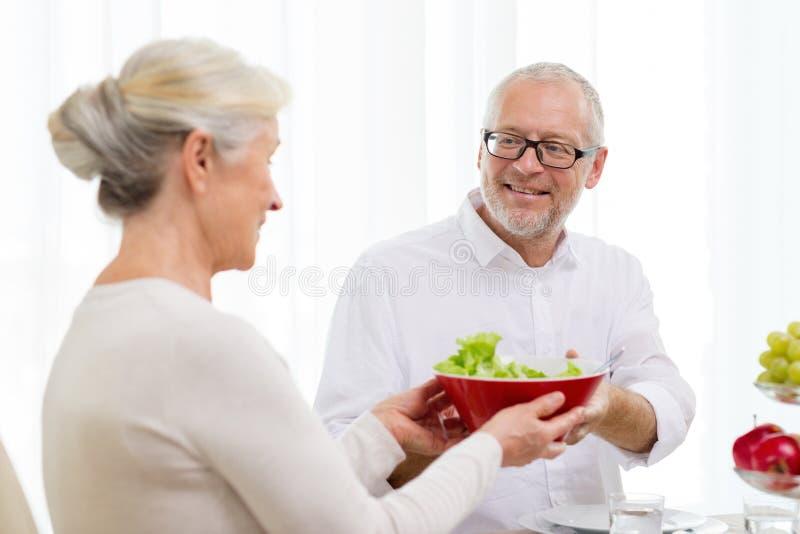 Glimlachend hoger paar die diner hebben thuis stock foto's