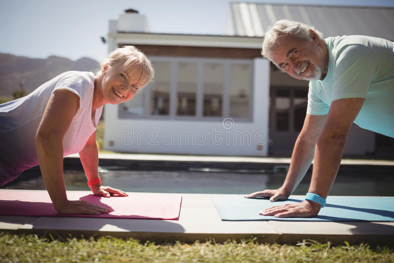 Glimlachend hoger paar die opdrukoefening dichtbij zwembad doen royalty-vrije stock foto