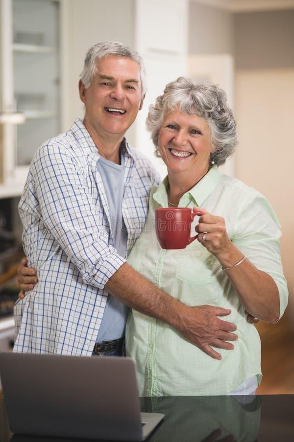 Glimlachend hoger paar met koffiekop die door laptop zich thuis bevinden stock afbeelding