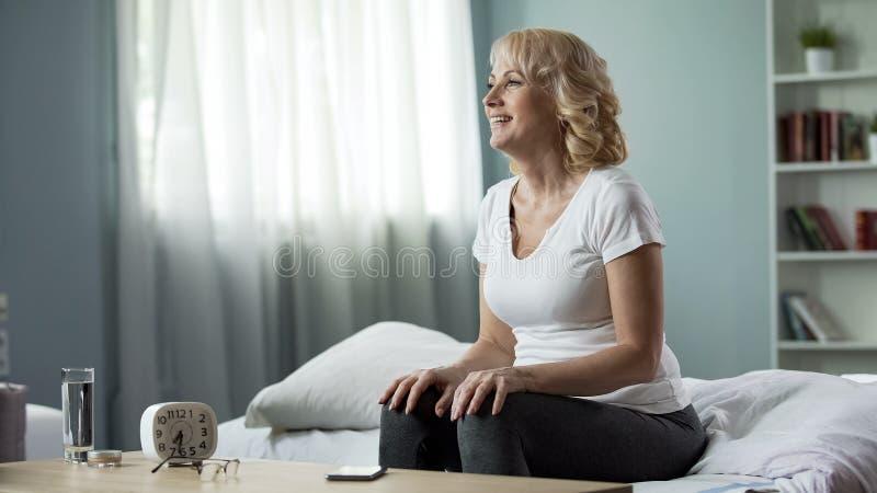Glimlachend hogere damezitting op bed thuis, positieve houding, gezondheid en schoonheid stock afbeeldingen
