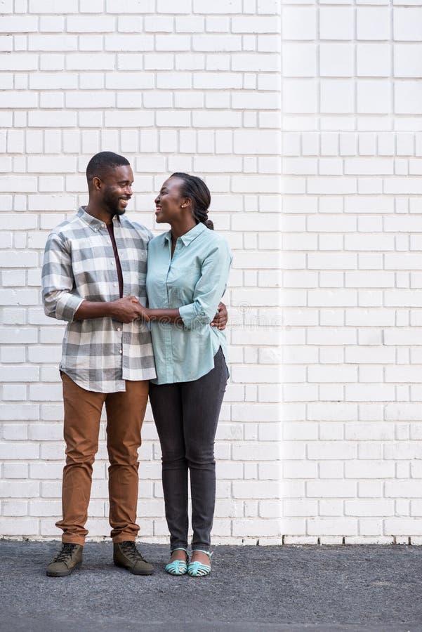 Glimlachend jong Afrikaans paar die in de stad zich verenigen royalty-vrije stock foto