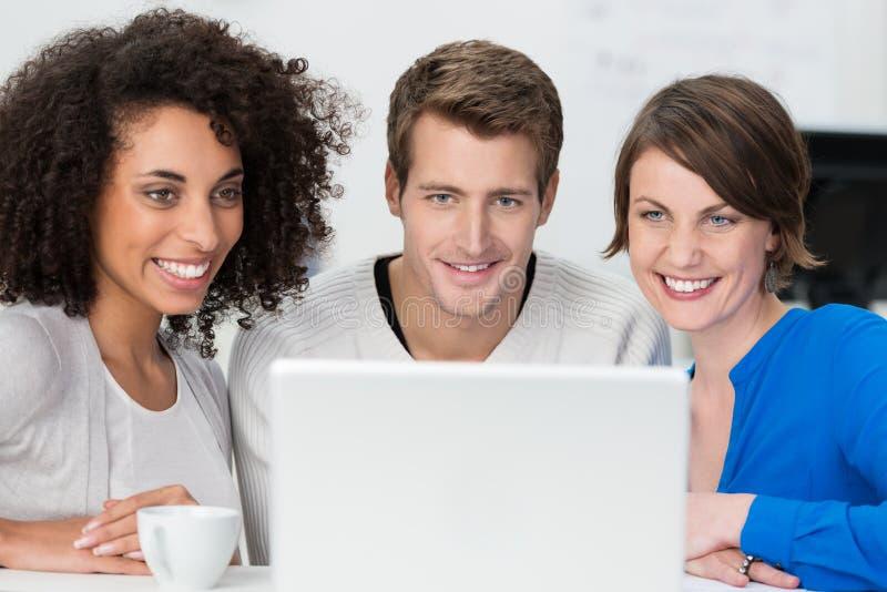 Glimlachend jong commercieel team die samenwerken royalty-vrije stock afbeeldingen