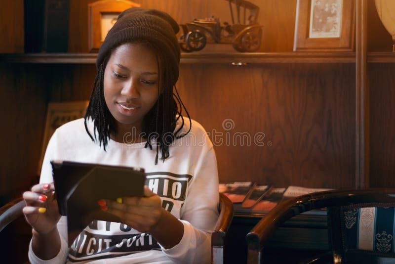 Glimlachend jong gelukkig zwart Afrikaans Amerikaans meisje die aan tablet werken stock afbeeldingen