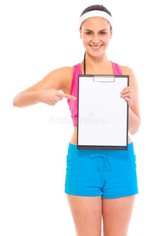 Glimlachend jong geschikt meisje dat op leeg klembord richt stock afbeelding