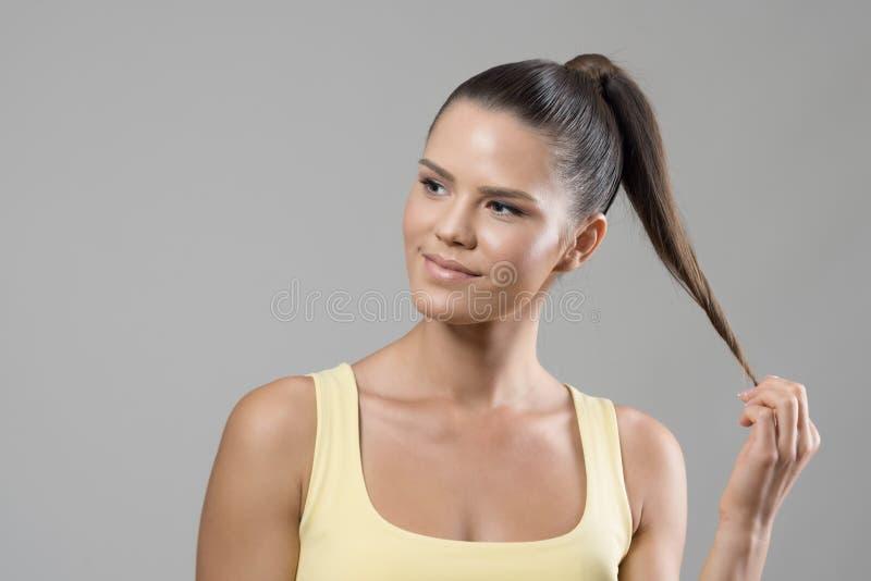 Glimlachend jong geschikt sportief vrouwelijk model tollend haarslot die weg eruit zien stock foto