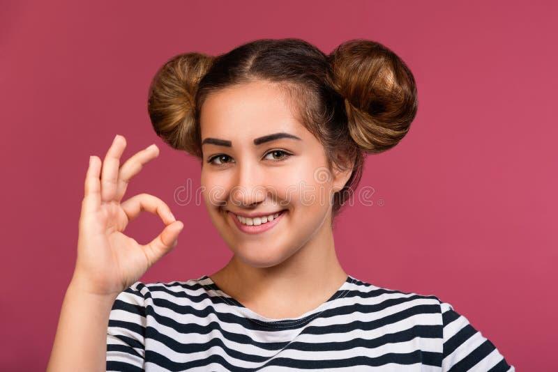 Glimlachend jong hipstermeisje met speels kapsel die o.k. die handgebaar maken over roze achtergrond wordt geïsoleerd royalty-vrije stock afbeeldingen