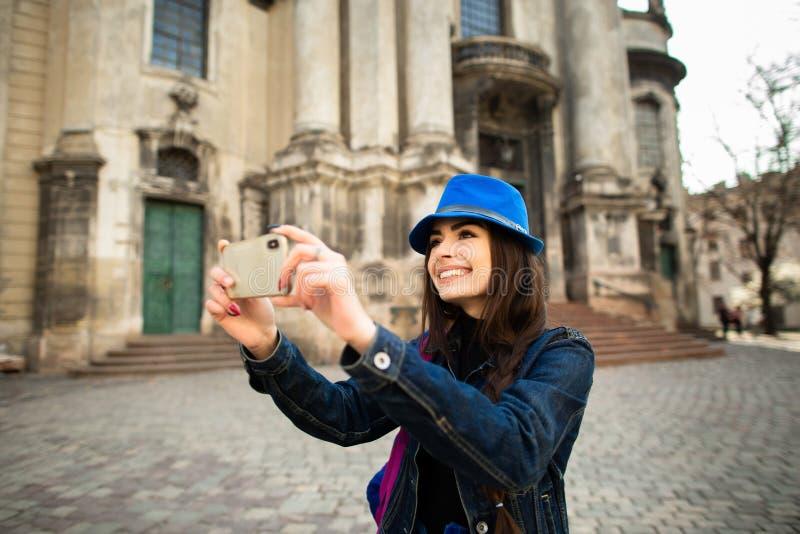 Glimlachend jong meisje die beelden van de architecturale monumenten van de oude stad Lviv nemen ukraine royalty-vrije stock foto's