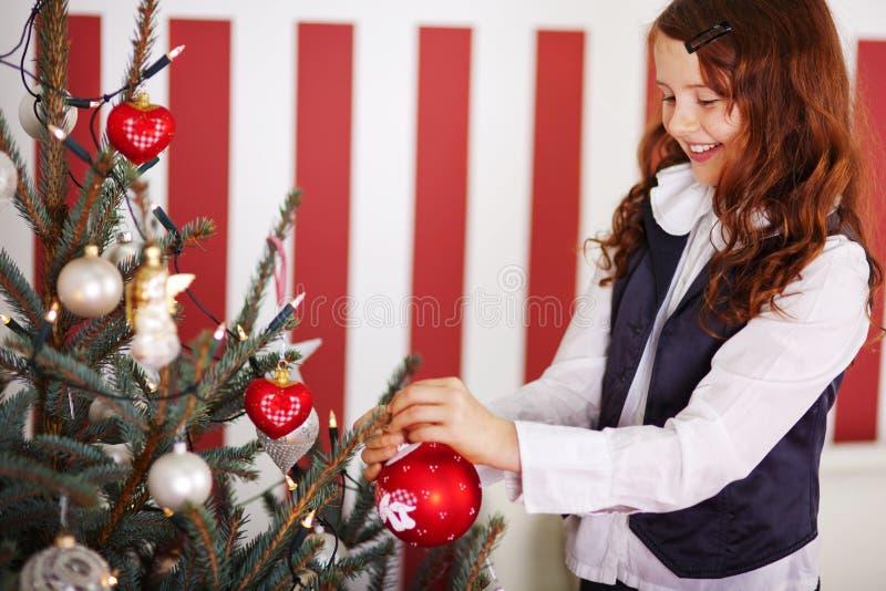 Glimlachend jong meisje die de Kerstboom verfraaien stock afbeeldingen