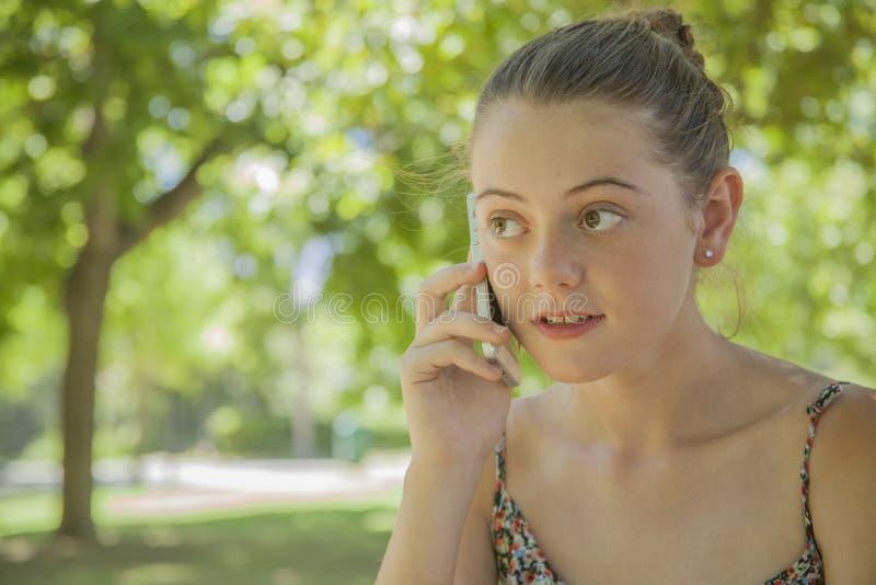 Glimlachend jong meisje die een celtelefoon uitnodigen royalty-vrije stock foto