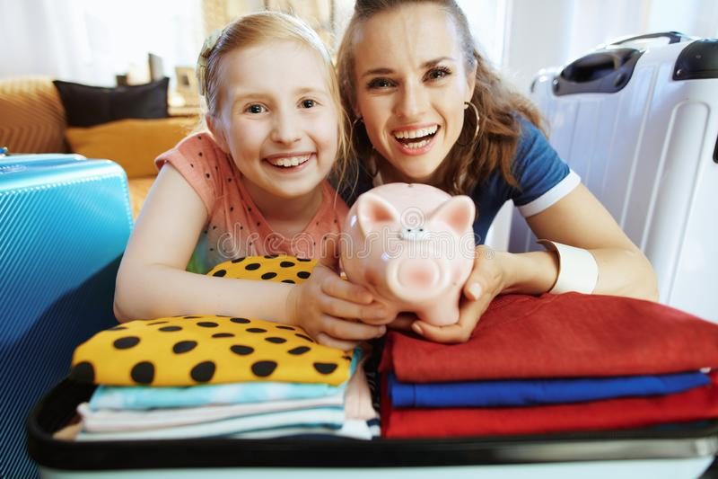 Glimlachend jong moeder en kind die spaarvarken tonen royalty-vrije stock afbeeldingen