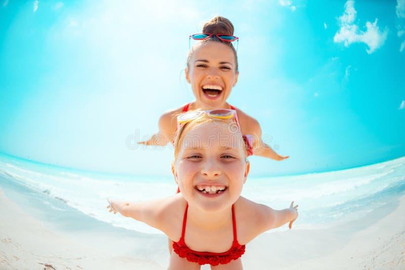 Glimlachend jong moeder en kind op kust die prettijd hebben royalty-vrije stock afbeeldingen