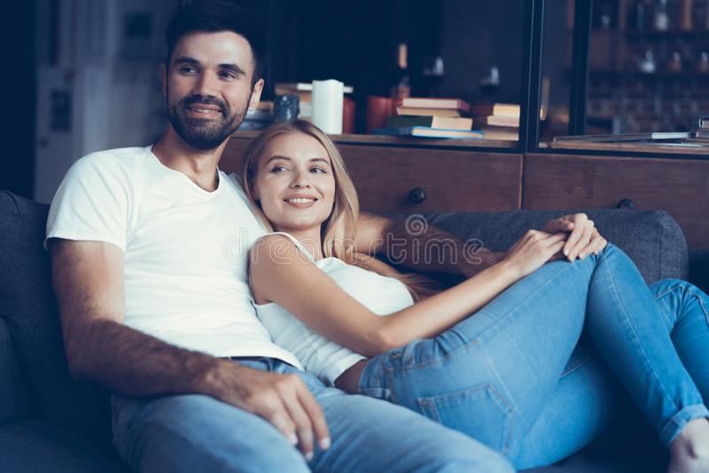 Glimlachend jong paar die en op TV thuis ontspannen letten stock fotografie