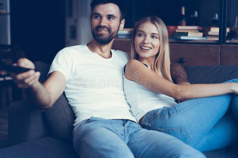Glimlachend jong paar die en op TV thuis ontspannen letten royalty-vrije stock foto's