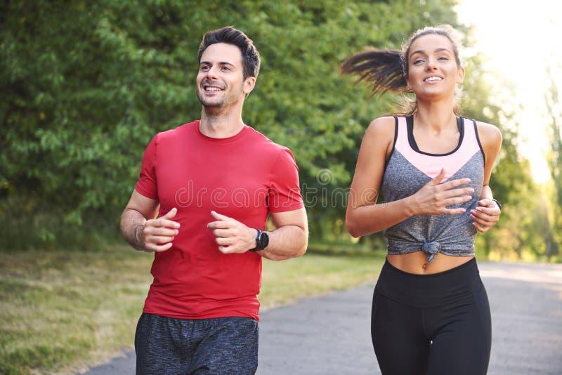 Glimlachend jong paar die in het park lopen stock foto's