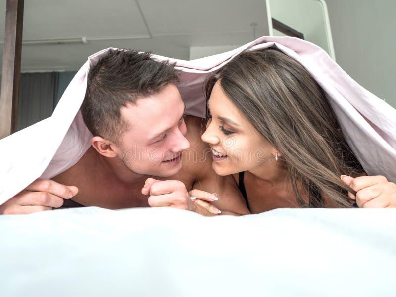 Glimlachend jong paar die onder de sprei in bed liggen royalty-vrije stock foto's