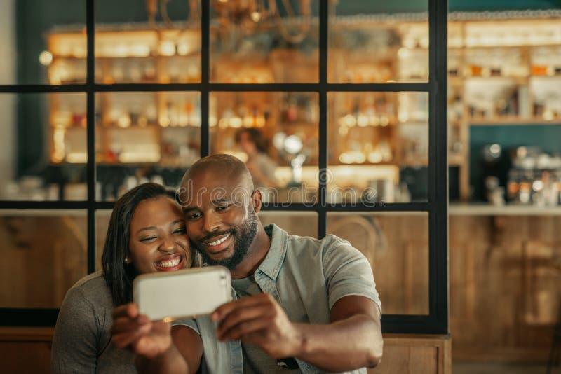 Glimlachend jong paar die selfies samen in een bar nemen stock fotografie