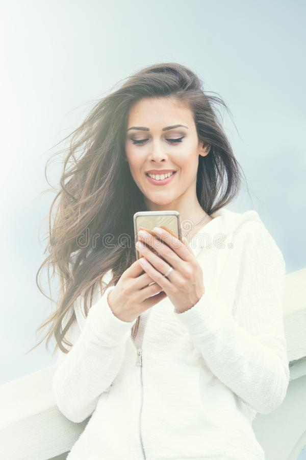 Glimlachend jong stedelijk meisje met smartphone in de witte dag van de sweaterzomer in stad stock foto's