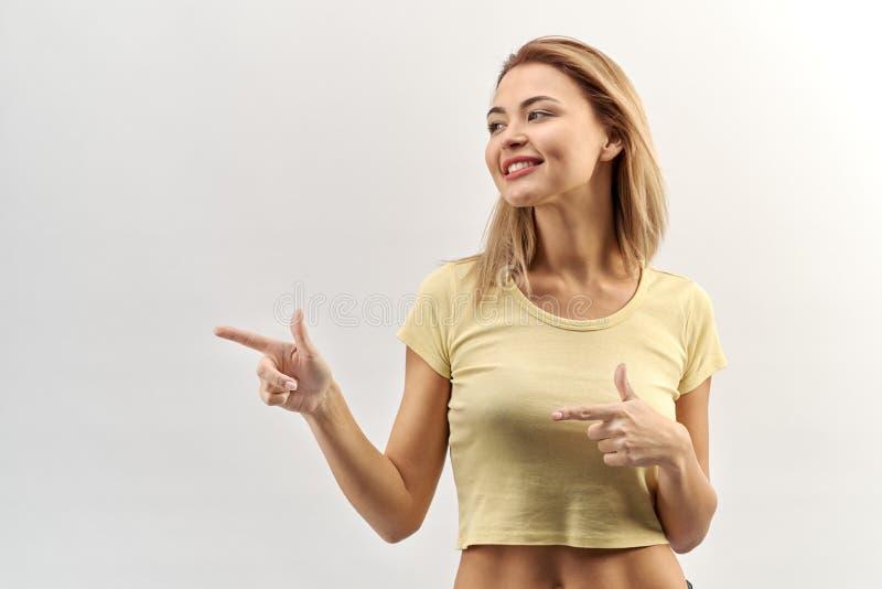 Glimlachend jong vrouwenmeisje in het korte lichtgele t-shirt kijken stock afbeeldingen