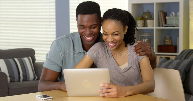 Glimlachend jong zwart paar die tablet samen gebruiken stock foto's