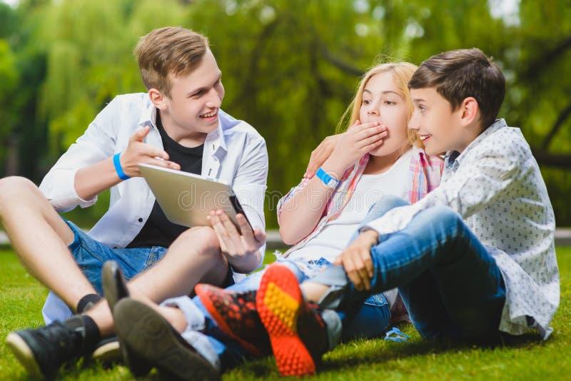 Glimlachend jonge geitjes die pret hebben en bekijk aan tablet gras Kinderen die in openlucht in de zomer spelen de tieners delen stock afbeeldingen