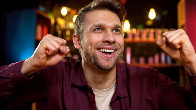 Glimlachend Kaukasisch mannetje die favoriet team het noteren doel, winst in toernooien vieren royalty-vrije stock foto