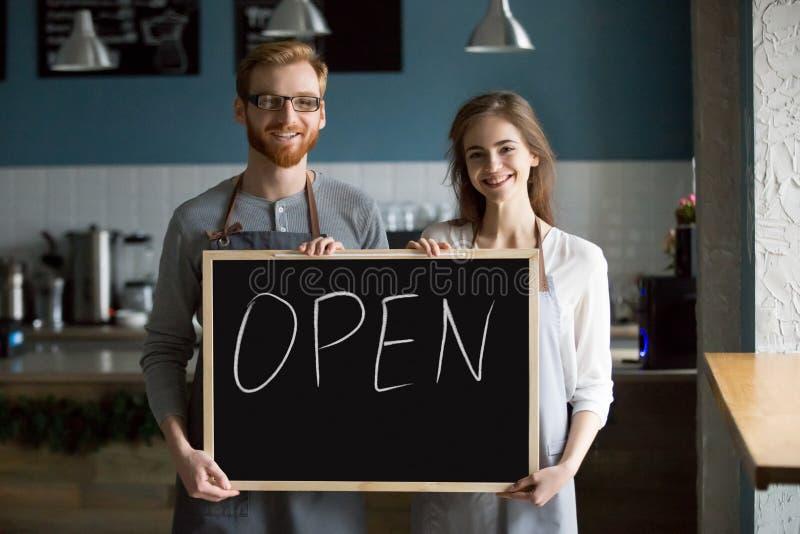 Glimlachend kelner en serveersterholdingsbord met open teken, p royalty-vrije stock afbeeldingen