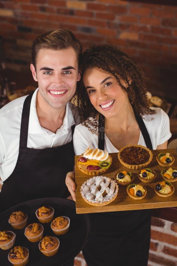 Glimlachend kelner en serveersterholdingsdienblad met muffins royalty-vrije stock afbeeldingen