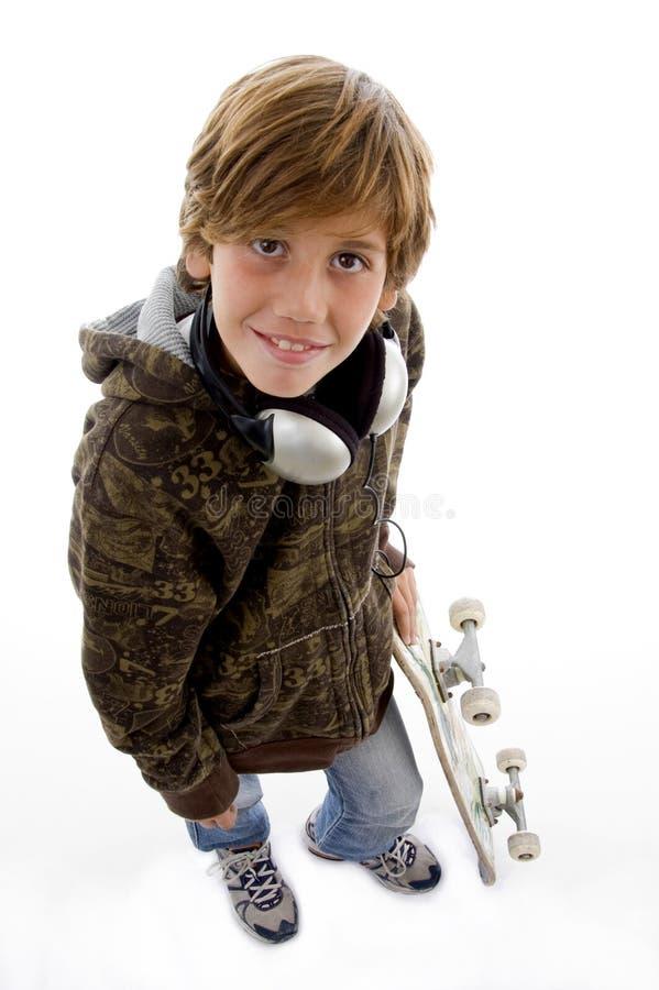 Glimlachend kind met skateboard en hoofdtelefoon stock foto