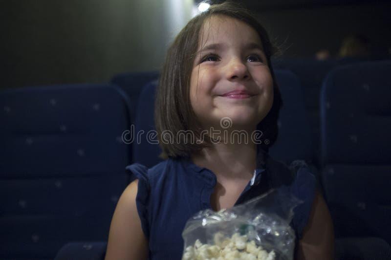 Glimlachend kindmeisje bij bioskoop Echte scène stock afbeeldingen