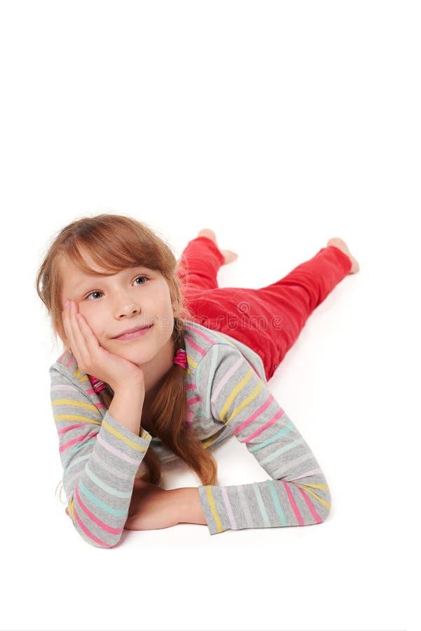 Glimlachend kindmeisje die op maag op de vloer liggen royalty-vrije stock afbeeldingen