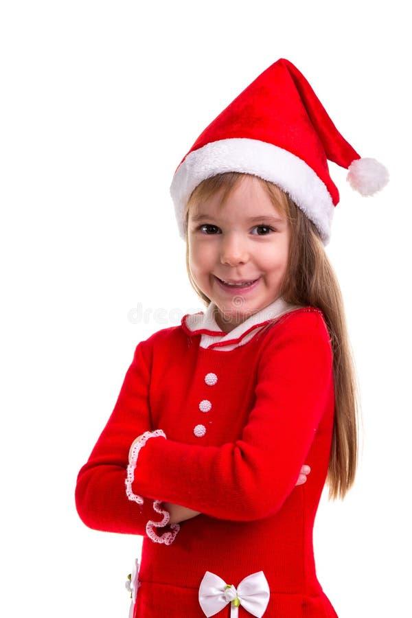 Glimlachend koket Kerstmismeisje die die een santahoed dragen over een witte achtergrond wordt geïsoleerd Portretbeeld stock foto's