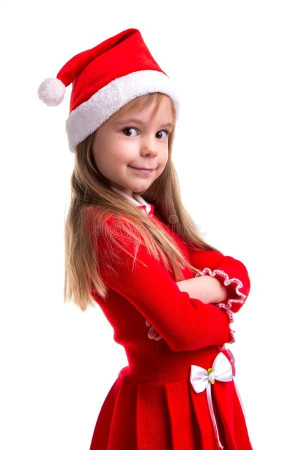 Glimlachend koket Kerstmismeisje die die een santahoed dragen over een witte achtergrond wordt geïsoleerd, die zich in de halve d royalty-vrije stock foto