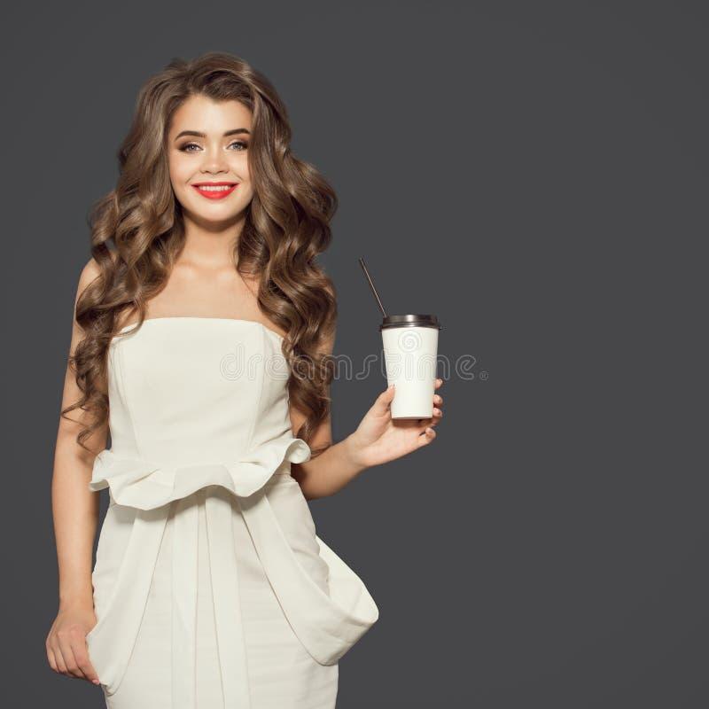 Glimlachend kop van de vrouwenholding van koffie de meeneem Grijze achtergrond stock afbeelding