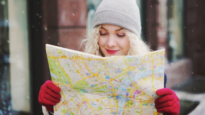 Glimlachend krullend blond meisje met kaart, de winter stock afbeelding