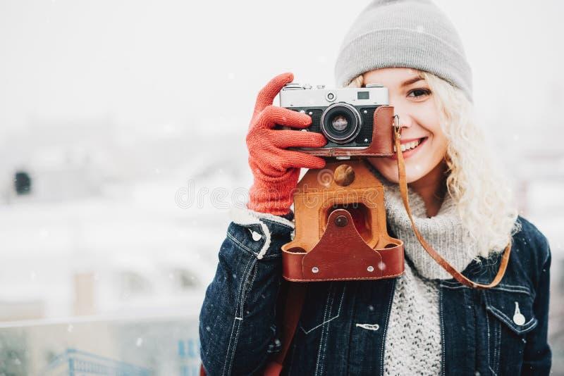 Glimlachend krullend blond meisje met retro filmcamera royalty-vrije stock afbeelding