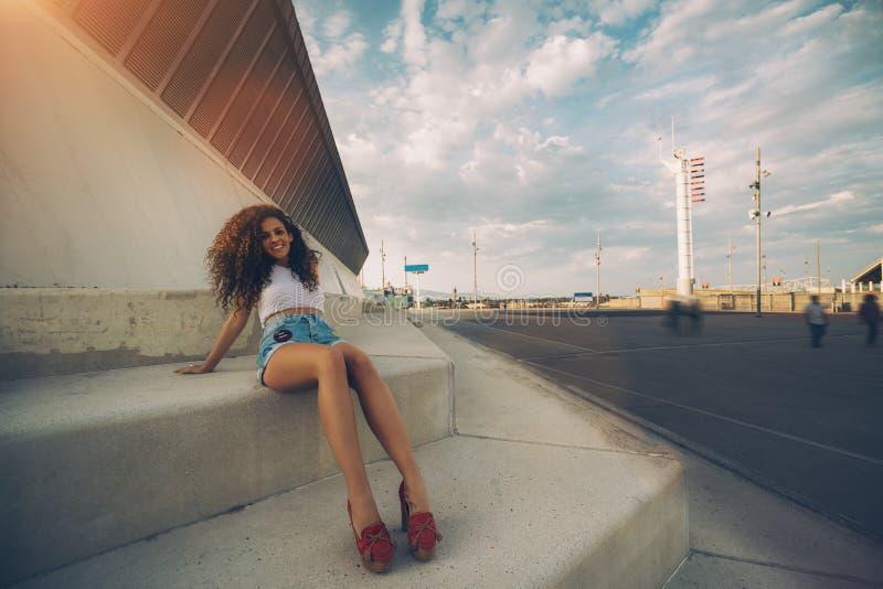 Glimlachend krullend meisje in stedelijke montages royalty-vrije stock foto's