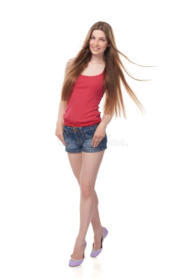 Glimlachend langbenig jong wijfje in denimborrels en rode bovenkant met mooi lang haar stock foto