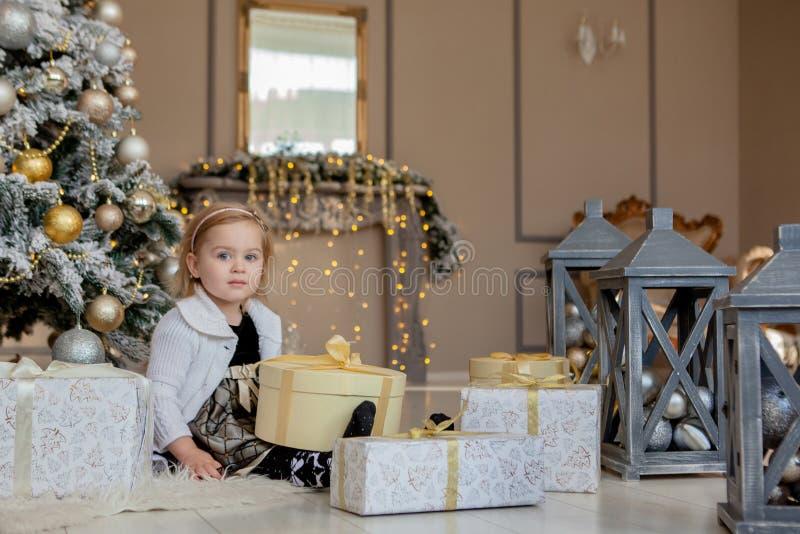 Glimlachend leuk meisje die een Kerstmisgift, de achtergrondkerstboom openen stock fotografie