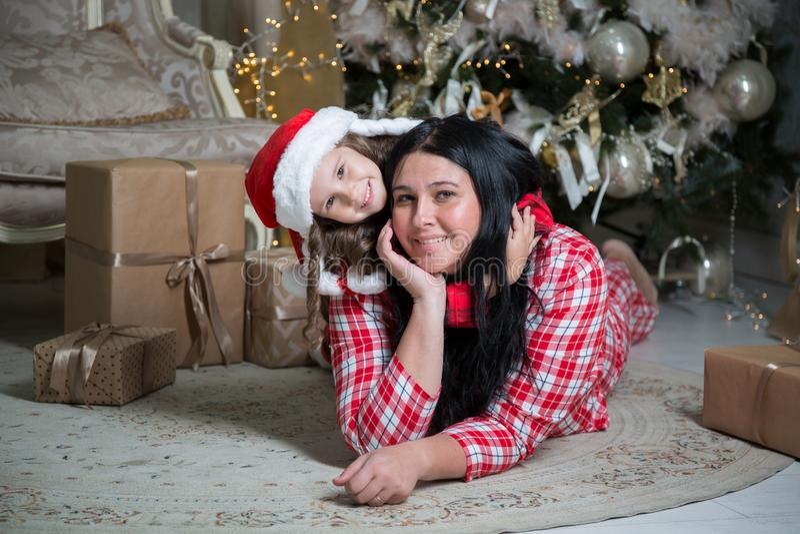 Glimlachend leuk meisje met santahoed en moeder dichtbij giften en Kerstboom Nieuwe jaar of Kerstmisfamilieviering thuis stock foto