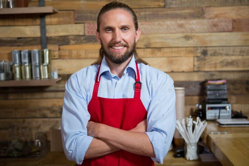 Glimlachend mannelijke barista bevindende die wapens in cafetaria worden gekruist stock fotografie