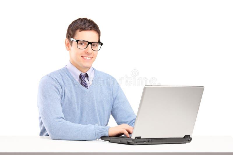 Glimlachend mannetje dat aan laptop werkt stock fotografie