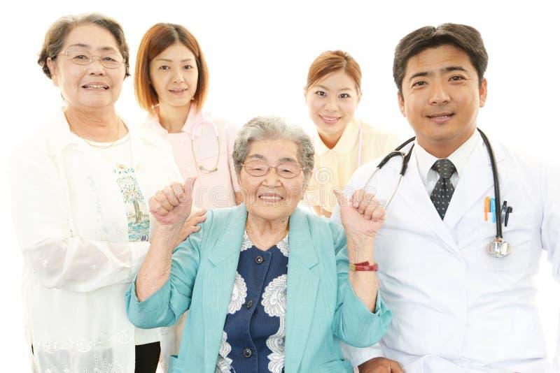 Glimlachend medisch personeel met oude vrouwen stock foto's