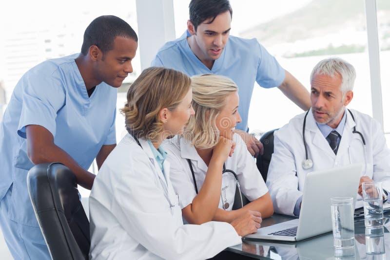 Glimlachend medisch team die laptop met behulp van royalty-vrije stock foto's