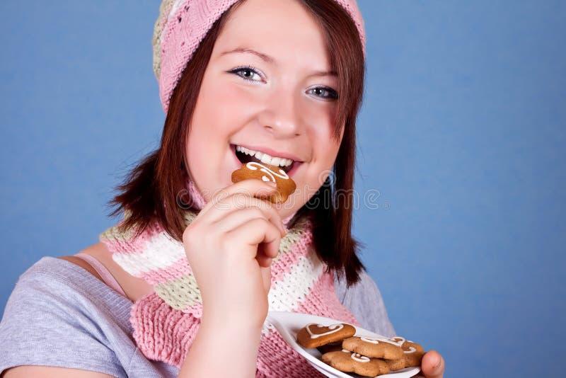 Glimlachend meisje dat een koekje eet royalty-vrije stock afbeelding