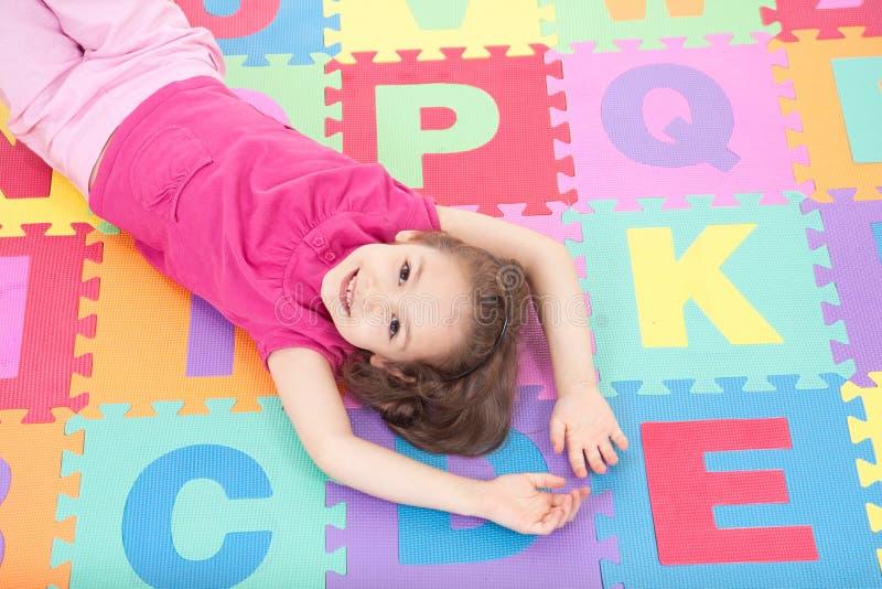 Glimlachend meisje dat op alfabettegels ligt royalty-vrije stock foto's