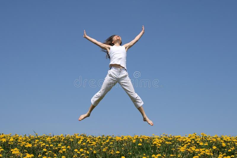 Glimlachend meisje dat op gebied springt stock foto