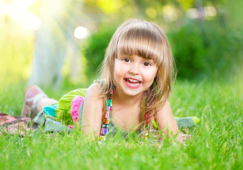 Glimlachend meisje dat op groen gras ligt royalty-vrije stock foto's