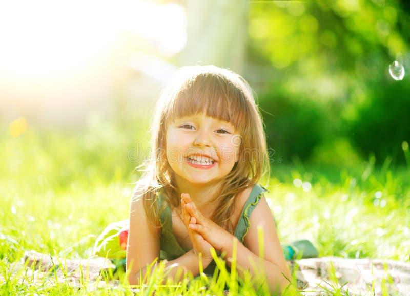 Glimlachend meisje dat op groen gras ligt royalty-vrije stock afbeelding