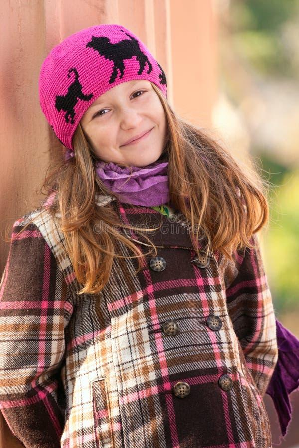 Glimlachend meisje dat zich dichtbij de kolom bij het park bevindt stock foto